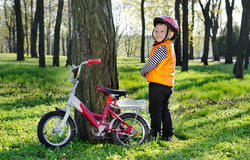 Little boy standing grinning alongside his bicycle Stock Photo