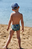Little boy standing with her back to the beach Stock Photo