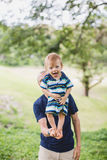A little boy standing on his father, balancing Stock Photo