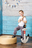 Little boy standing and holding an anchor Stock Images