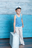 Little boy standing and holding suitcase Stock Photography