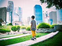 Little boy standing looking the buiding  in the city park Royalty Free Stock Images