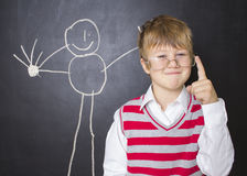 Little boy standing near the blackboard for drawing. A boy stands near the blackboard for drawing. The child in a white shirt , striped vest and glasses . He Royalty Free Stock Photography