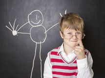 Little boy standing near the blackboard for drawing. A boy stands near the blackboard for drawing. The child in a white shirt , striped vest and glasses . He Stock Image