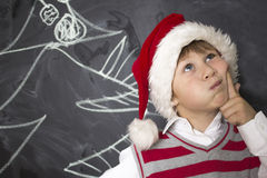 Little boy standing near the boards. Boy in Christmas hat . He keeps his finger beside his cheeks and looks upwards. A child in a white shirt and a striped Royalty Free Stock Photo