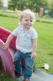 The little boy standing near children's slides Stock Image