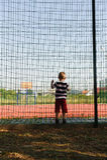 Little boy standing near grid fence Stock Image