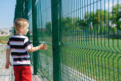 Little boy standing near grid fence Stock Photos