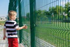Little boy standing near grid fence Stock Photos