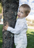 Little boy standing near the tree. In the park Royalty Free Stock Photo