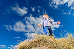 Little boy standing on a pile of hay on the background of blue sky Stock Photos