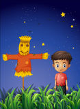A little boy standing beside the scarecrow Royalty Free Stock Photos