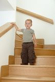 Little boy standing on stairs. Worried little boy standing on stairs, leaning on hand rail Stock Photo