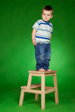 Little boy standing on stairs in studio Stock Photos