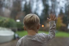 Little boy standing staring out of a window. In evening light into the garden with his hand spread out on the glass viewed from behind Stock Images