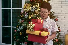 Little boy standing and surprise while holding a lot of gift box from Christmas party in living room royalty free stock images