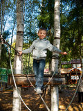 Little boy standing on a tightrope. On the background of two birch trees Royalty Free Stock Image