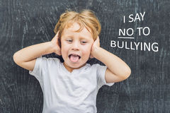 Little boy standing up for himself and saying NO to bullying by blowing a raspberry at the bully in front of a blackboard at schoo stock image