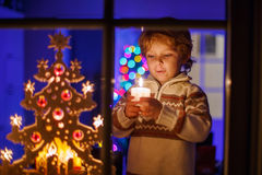 Little boy standing by window at Christmas time and holding cand Royalty Free Stock Photography