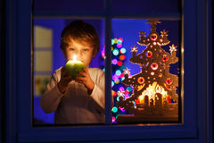 Little boy standing by window at Christmas time Royalty Free Stock Photography