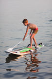 SUP (stand up paddle) learning. Little boy standing on the windsurfing board with paddle. Evening light Royalty Free Stock Image