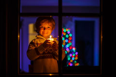 Little boy standing by winter at Christmas time and holding cand Stock Image