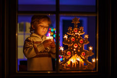 Little boy standing by winter at Christmas time and holding cand Royalty Free Stock Photography