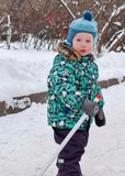 A little boy stands with a hockey stick in winter in a snowy park stock image