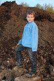 Little boy stands on earthen embankment royalty free stock photo