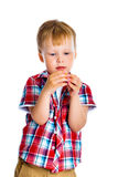 Little boy stands and examines small toy Royalty Free Stock Photography