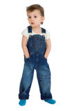 Little boy stands in jeans overalls. A little boy standing in a denim suit on a white background Royalty Free Stock Photo