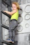 A little boy stands on a ladder Stock Photo