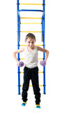 Little boy stands next to the stairs and horizontal bars and holds in hands dumbbell Royalty Free Stock Photo