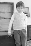 A little boy stands in an old trunk. Stock Photos