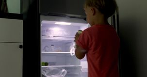 Small child stands open refrigerator takes milk