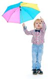 Little boy stands under a colorful umbrella. Royalty Free Stock Photo