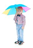 Little boy stands under a colorful umbrella. Stock Image