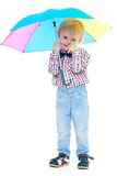 Little boy stands under a colorful umbrella. Royalty Free Stock Photos