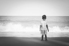 Little boy stanging looking the sea,black and white tone Royalty Free Stock Photo