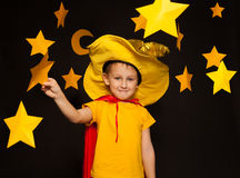 Little boy in stargazer costume among paper stars Royalty Free Stock Photos