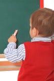 Little boy starts drawing on chalkboard stock photography