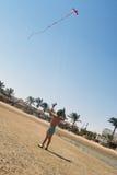 The little boy starts a kite Royalty Free Stock Photos