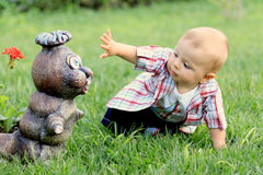 Little boy with a statue in a garden backyard Stock Images