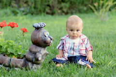 Little boy with a statue in a garden backyard Royalty Free Stock Photography
