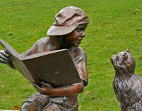 Little Boy Statue Reading to Cat. Cast bronze statue of boy reading a book to a listening cat Stock Image