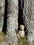 Little boy statue beside tree Royalty Free Stock Photo