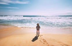Little boy stay on ocean beach in sunny day Stock Photos
