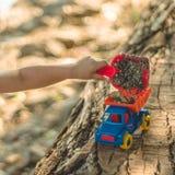 Little Boy-Steigen Kind gießen wir den Sand in den roten LKW Junge der Kinderstraßen-Spiele A, der mit einer Maschine auf dem gro stockfoto