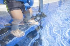 Little boy steps down the swimming pool ladder with foot underwa. Ter. He wears a float belt Stock Photo