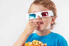 Little boy in stereo glasses eating popcorn Stock Image